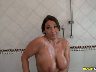 She stands naked in a shower soaping her succulent boobs. She catches the dude spying on her while she is taking a shower. She invites him indoors and