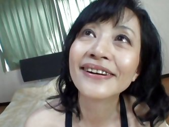 The brunette mature Nippon takes off her clothes in front of me but this whore is still not naked. She takes a sit on the bed and looks at me, her slu