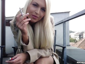 Stunning busty hot German blonde babe rubs her wet pussy outside, on her balcony while she smokes a cigarette.