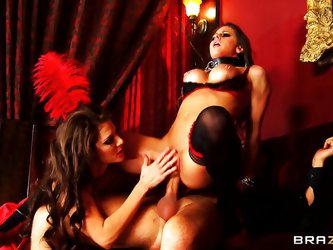 Two beautiful brunettes with amazing breasts kiss themselves while on a man's lap then they give him a blowjob. One of them begins to ride his hu