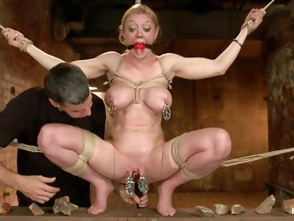 Tied with ropes, ball gagged and with metal clamps on her nipples and pussy lips the hot blonde screams and moans frenetically as the executors give h