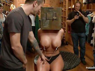 This sexy blonde milf is being humiliated, by a group of men. She has a safe on her head, so she can't see, and she is paraded around. One man pu