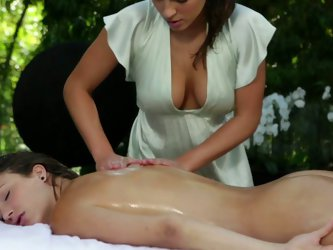 Gorgeous brown haired beauty gets her whole body covered with massage oil and then sexy masseuse properly massages her appetizing pussy.