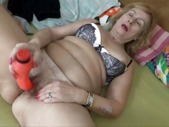Granny Emmy keeps a hot bush between her thighs. Her tight, unshaved vagina needs a serious fuck so she grabs her red dildo after pinching her nipples