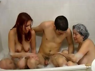 Horny stud sucks on one BBW grandma's big saggy tits. Old granny gives him a blowjob while young redhead babe watches it and masturbates.