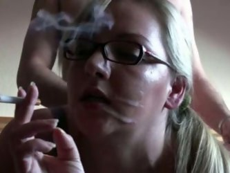 Fat blonde babe with glasses smokes  cigarette as she gets fucked in her butt hole and in her pussy from behind by her man.