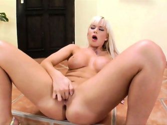 Blonde with fake tits prods her snatch with a long glass toy