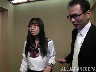 Busty Asian wearing glasses gives a hot titjob to a horny man