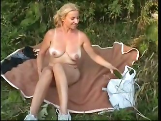 Horny busty light-haired mature whore with sagged boobs lies in the field and shoves big cucumber in her ugly hairy pinkish snutch.