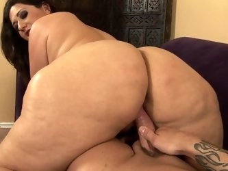 A big ass milf with a hairy pussy is getting penetrated on the sofa