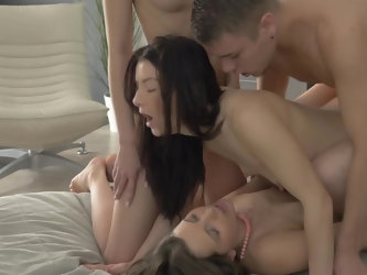 Beauteous chick drinks wine hugging her boyfriend and watching two other female having fun in bed. Soon she asks young man to join girlfriends and hav