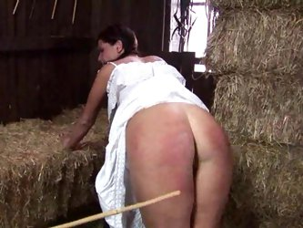Her ass is caned by two guys