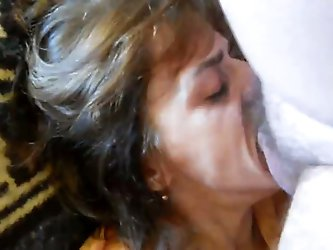 Take a look at my mature skank. She lies on couch while I fuck her mouth with my thick hairy cock. She sucks me off balls deep and carefully bites my