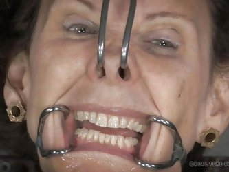 This slave is in such pain. She has hooks in her nose that pull on her nostrils. The masters puts hooks in her mouth so she has to submissively show h