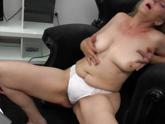 This horny mature is lost in her masturbation. Look how this naked slut who is only in her panties moans while she is crushing her nice pair of boobs.