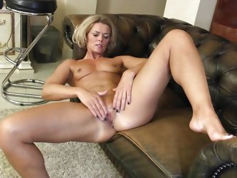 This hot milf feels kinda lonely. She is lying on her couch and starts touching her own nipples. She takes her black nylon panties off and spreads her