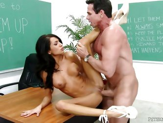 This dirty slut is in Peter North's classroom. He bends her over the desk and fucks her like crazy with his massive cock. He pulls out of her pus