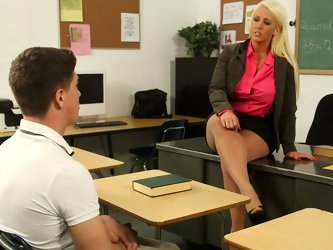 Whorish long haired tanned blondie wanna punish her naughty and spoiled student. So slutty teacher lies right onto the desk playing with her big boobs