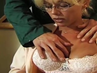 Provocative teacher wearing sexy blouse and having d-cup boobs makes student horny. He starts to feel up her big jugs and puts her on table to give he