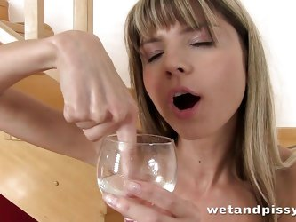 Gina pulls down her jean shorts on the stairs and spreads her pussy open wide. She takes a wine glass and pisses inside of it. She pours the piss onto