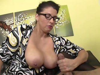 Busty mom gives warm handjob on a young dick