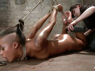 Skin Diamond is a ebony tattooed milf. As you can see, the gorgeous female is tied up with ropes, hanging on that ceiling. She must suffer for all the