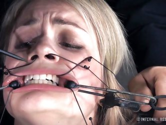 Watch as this blonde slave is locked into the stocks and tortured by her master. He puts clamps on her mouth and pulls them apart so her mouth is gape