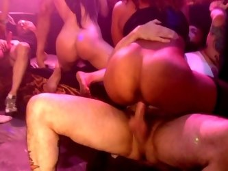 Several girls are with some guys in a seedy club, fucking around